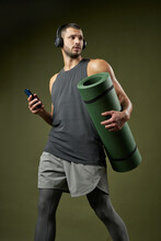 Bearded Fitness Trainer Holding Smartphones In Arm Rushing To The Practice Isolated On Green Background Of A Studio
