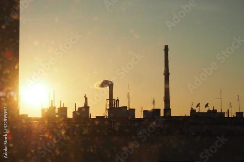 Fototapeta Pomarańczowy zachód słońca nad miastem wśród dachów obraz