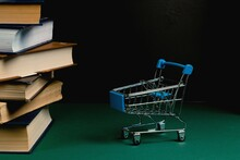 A Stack Of Books And A Grocery Cart On A Green Background. Bookstore, Sales Concept