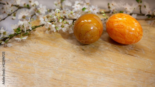Obraz Easter eggs painted by hand and a brunch of white cherry blossoming flowers on light wooden background. Close up. - fototapety do salonu