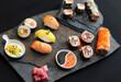 Sushi rolls nigiri, uramaki, hosomaki with salmon  and mango  with soy sauce in a black  stone background
