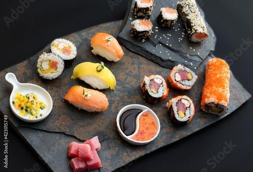 Fototapeta Sushi rolls nigiri, uramaki, hosomaki with salmon  and mango  with soy sauce in a black  stone background obraz