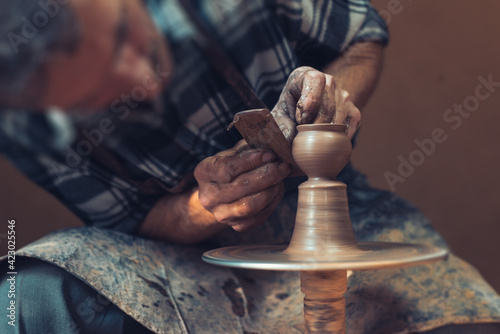 Fotografering A male artisan in a pottery workshop makes a piece of clay behind a pottery wheel