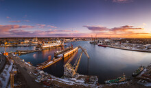 Ship Repair And Maintenance Docks In Beautiful Sunset Colors. Giant Cargo Vessel Being Repaired At Dockyard In Riga.