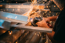 An Adult Man Is Seen Working Cutting A Piece Of Metal In An Industrial Workshop, Sparks Are Seen