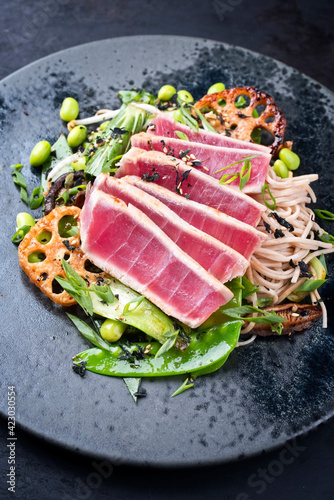 Modern style traditional Japanese gourmet seared tuna fish steak tataki with soba noodles and stir-fried vegetables served as close-up on a Nordic design plate