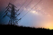 The silhouette of the high voltage transmission tower has a complex steel structure. High voltage pole silhouette In the meadow there is a background of the night sky and the milky way.