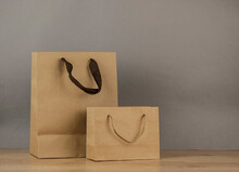Set Blank Brown Paper Carrier Bags With Handles For Shopping On Wood Table