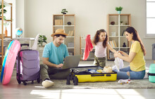 Happy Family Of Three Going To Travel. Father Choosing Tour, Buying Ticket Or Reserving Hotel Online Using Laptop. Mother With Preschool Daughter Packing Clothes In Suitcase Luggage Bag. Home Interior