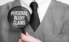 Businessman With Magnifying Glass On The White Background. Personal Injury Claims Sign