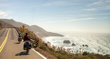 Two Cross Country Bikers Pedal Down The Pacific Coast Highway With The Crashing Surf Of The Pacific In The Background.