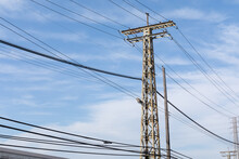 Old Industrial Metal Electrical Power Tower, Weathered And Rusty, Strung With Electrical Lines Against A Bright Blue Sky With Clouds, Horizontal Aspect