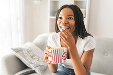 Portrait Of Teenager Watching Tv With Pop Corn On Hand