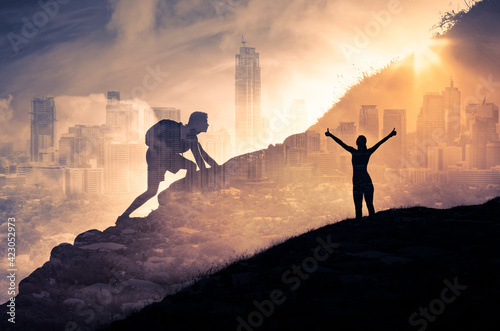 Silhouette of a person climbing to the top of a mountain. Female with arms up to the sky. Strong man, and woman, Winning, success , inspiration and life goals concept.