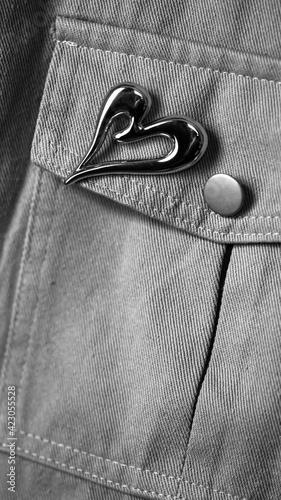 Fotografia denim jacket pocket with metal heart brooch, black and white image