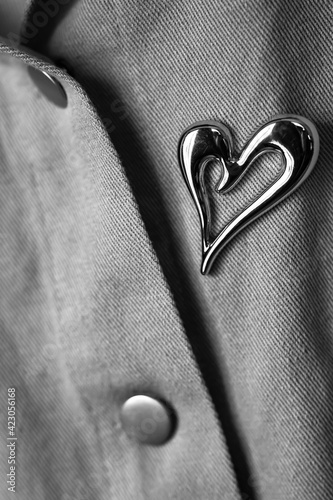 Canvas monochrome image of a fragment of a denim jacket with a metal brooch in the shap