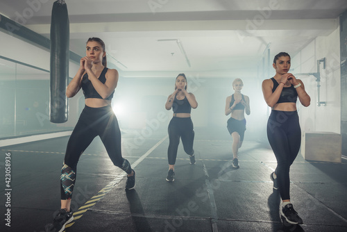 Obraz na plátne Group of sportswomen in sportswear doing lunge exercise at the gym with their ri