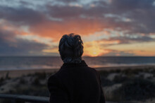 Back View Of Elderly Female Traveler In Casual Clothes Standing On Wooden Pier On Sandy Beach And Enjoying Seascape At Sunset
