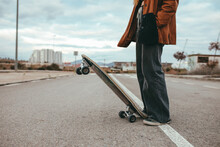 Side View Of Crop Female Skater In Trendy Outfit Standing On Asphalt Road With Cruiser Skateboard In Countryside