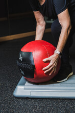 Crop Anonymous Senior Female Athlete In Sports Clothes Leaning Forward While Taking Medicine Ball During Workout In Gymnasium