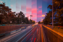 Asphalt Roadways With Driving Vehicles Between High Trees Under Bright Cloudy Sky In Town At Sundown