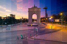 Stone Arch With Sculptures Between Trees And Light Posts Illuminating Roadways With Transport Traffic In Madrid At Sunset