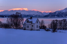 Lonely Residential Cabin Located On Shore Of Lake On Background Of Snowy Mountain Range Lit By Pink Sunset Light In Winter In Norway
