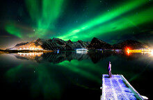 Unrecognizable Person Standing On Pier And Admiring Scenery Of Green Polar Lights Glowing In Night Starry Sky Above Mountains In Winter In Norway