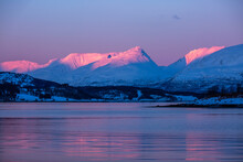 Picturesque View Of Calm Sea Under Cloudless Sundown Sky In Mountainous Terrain In Winter In Norway