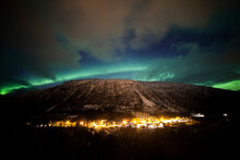 Breathtaking Scenery Of Mountainous Village At Night Under Sky With Glowing Green Northern Lights In Winter In Norway