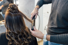 Crop Unrecognizable Male Stylist In Casual Clothes Using Hair Straightener While Doing Curls For Female Client In Beauty Salon