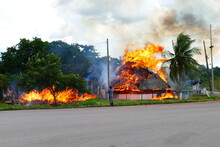 In Bright Flames Burning Indian Hut Made Of Wood And Dried Palm Leaves Of Indigenous People In Brazil.