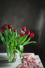 Glass Vase With Red Tulips On The Table By The Window