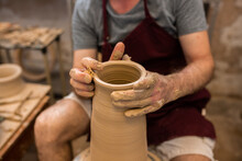 Crop Unrecognizable Sculptor With Equipment Giving Shape While Sculpting With Brown Clay On Throwing Wheel