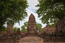 Scenery Of Authentic Oriental Wat Phra Mahathat Temple With Stone Buddha Statues Amidst Lush Verdant Trees In Thailand