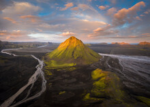 Establishing Shot Of Vast Valley Covered With Grass And Many Narrow Curvy Rivers Near Rough Desolated Hills Against Blue Sky In Iceland