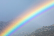 Vivid Rainbow On Cloudy Sky Over Mountain Ridge