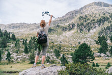 Back View Anonymous Female Hiker In Casual Clothes With Backpack Raising Hand With Nordic Walk Poles While Standing On Stony Hilltop In Mountainous Ruda Valley In Catalan Pyrenees