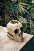 Ceramic Polynesian Tiki Cup Skull Shaped With Straw Placed On Wooden Table On Blurred Background