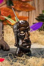 Brown Sculptural Tiki Mug With Alcohol Drink Decorated With Straw And Ice Placed On Table