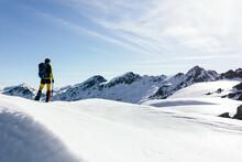 Full Body Back View Of Unrecognizable Male Mountaineer In Warm Activewear With Backpack Standing On Slope Of Snowy Rocky Mountain And Enjoying Spectacular Landscape In Sunny Winter Day