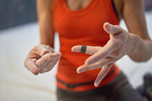 Crop Unrecognizable Female In Sportswear Demonstrating Hands In Chalk And Blood After Training In Bouldering Center