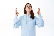 Hopeful Smiling Girl Looking Up While Making Wish, Cross Fingers For Good Luck, Praying God To Pass Exam, Pleading For Dream Come True, Standing Against White Background