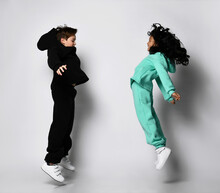 Trendy Active Overjoyed Interracial Sportive Boy And Girl In Warm Sportswear Jumping Together. Full-length Portrait Caucasian And Asian Funky Kid. Friendship, Preteen Children Fashion, Cool Childhood