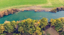 Drop Down View Of River Flowing Through Fields After Harvest.