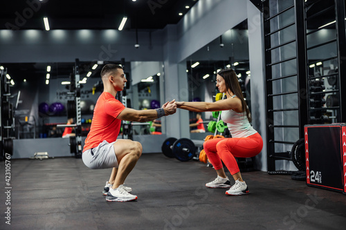 Fototapeta Two athletes, a beautiful woman and a handsome man are in a squatting position in the gym or fitness center. They look each other in the eyes and hold hands. Fitness lover, eye contact obraz