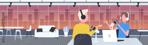 podcasters talking to microphones recording podcast in studio podcasting online radio concept man in headphones interviewing woman broadcasting portrait horizontal