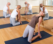 Group of people performing kneeling back-bending asana Ustrasana or Camel Pose during yoga course at gym