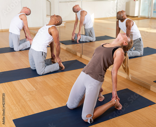 Foto Group of people performing kneeling back-bending asana Ustrasana or Camel Pose d