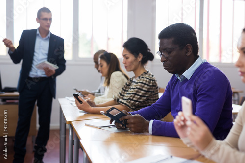 Young focused man listening to lecture taking notes at adult education class